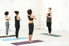 Grupo de mujeres multiculturales que practican yoga con el instructor de sexo masculino fotografía de archivo libre de regalías