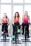 Grupo de mujeres que completan un ciclo en gimnasio Imagen de archivo