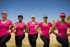 Grupo de mujeres que ejercitan junto en el campo de bota Fotografía de archivo libre de regalías