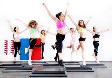 Grupo de mujeres que hacen aeróbicos en de pasos Fotos de archivo libres de regalías