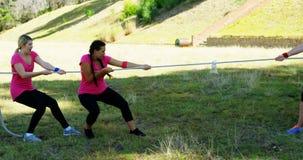 Grupo de mujeres que juegan esfuerzo supremo durante carrera de obstáculos metrajes