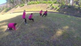 Grupo de mujeres que juegan esfuerzo supremo durante carrera de obstáculos que entrena a 4k almacen de video
