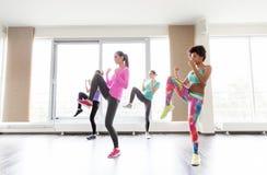 Grupo de mujeres que resuelven postura que lucha en gimnasio Imagen de archivo libre de regalías