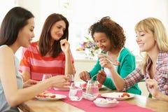 Grupo de mujeres que se sientan alrededor de la tabla que come el postre Foto de archivo libre de regalías