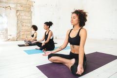 Grupo de mujeres que se sientan en las esteras de una yoga imagen de archivo
