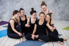 Grupo de mujeres que se sientan y que se relajan después de una clase larga de la yoga y que toman el selfie Imagen de archivo