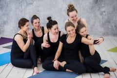 Grupo de mujeres que se sientan y que se relajan después de una clase larga de la yoga y que toman el selfie Foto de archivo libre de regalías