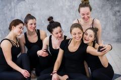 Grupo de mujeres que se sientan y que se relajan después de una clase larga de la yoga y que toman el selfie Fotografía de archivo