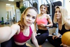 Grupo de mujeres que sonríen y que toman un selfie en el gimnasio foto de archivo libre de regalías