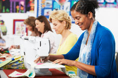Grupo de mujeres que usan las máquinas de coser eléctricas en clase imagen de archivo