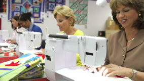 Grupo de mujeres que usan las máquinas eléctricas en clase de costura almacen de metraje de vídeo