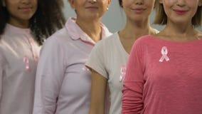 Grupo de mujeres sanas con las cintas rosadas que sonríen en la cámara, campaña anticáncer almacen de metraje de vídeo