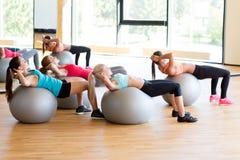 Grupo de mujeres sonrientes con las bolas del ejercicio en gimnasio Fotografía de archivo libre de regalías