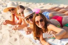 Grupo de mujeres sonrientes con smartphone en la playa Foto de archivo libre de regalías