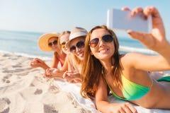 Grupo de mujeres sonrientes con smartphone en la playa Fotografía de archivo libre de regalías