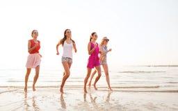 Grupo de mujeres sonrientes que corren en la playa Fotos de archivo