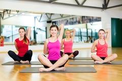 Grupo de mujeres sonrientes que estiran en las esteras en gimnasio Fotos de archivo