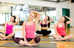 Grupo de mujeres sonrientes que estiran en las esteras en gimnasio Imagenes de archivo