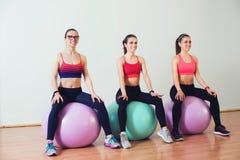 Grupo de mujeres sonrientes que hacen ejercicios en bola de la aptitud en gimnasio Imagen de archivo