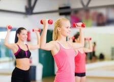 Grupo de mujeres sonrientes que se resuelven con pesas de gimnasia Fotografía de archivo