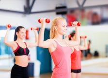 Grupo de mujeres sonrientes que se resuelven con pesas de gimnasia Imagen de archivo libre de regalías