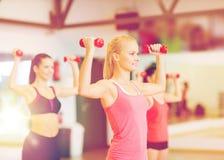 Grupo de mujeres sonrientes que se resuelven con pesas de gimnasia Fotos de archivo libres de regalías