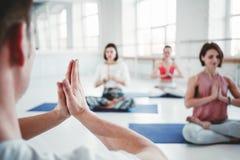 Grupo de mulheres adultas e de homem que fazem exercícios da ioga junto na classe da aptidão Os povos ativos praticam poses da io fotografia de stock royalty free