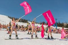 Grupo de mulheres bonitas felizes novas em um snowboard no biquini colorido com bandeiras Fotografia de Stock