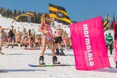 Grupo de mulheres bonitas felizes novas em um snowboard no biquini colorido com bandeiras Imagens de Stock Royalty Free