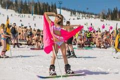 Grupo de mulheres bonitas felizes novas em um snowboard no biquini colorido com bandeiras Imagem de Stock