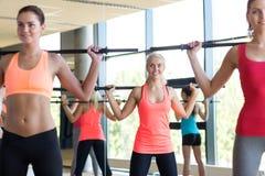 Grupo de mulheres com as barras no gym foto de stock royalty free