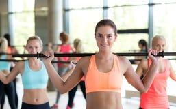 Grupo de mulheres com as barras no gym fotografia de stock royalty free