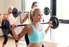 Grupo de mulheres com os barbells no gym Fotografia de Stock