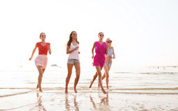 Grupo de mulheres de sorriso que correm na praia Fotos de Stock