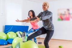 Grupo de mulheres desportivas alegres ativas que fazem únicas ocupas do pé com bola do equilíbrio que treina dentro no gym Fotografia de Stock Royalty Free
