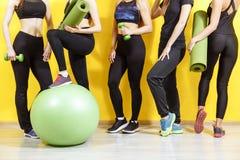 Grupo de mulheres desportivas novas que estão na parede Estudantes que tomam um resto da atividade da aptidão, hora de recuperar  foto de stock