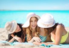 Grupo de mulheres felizes nos chapéus que tomam sol na praia Imagens de Stock