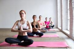 Grupo de mulheres novas no centro da ginástica yoga imagem de stock