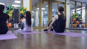 Grupo de mulheres que agitam a imprensa dentro do exercício da ioga da aptidão filme