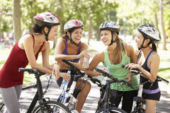 Grupo de mulheres que descansam durante o passeio do ciclo através do parque Imagens de Stock