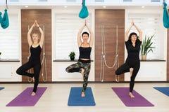 Grupo de mulheres que fazem exercícios da ioga no gym Estilo de vida do ajuste e do bem-estar fotos de stock royalty free