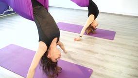 Grupo de mulheres que fazem a ioga do ar em redes no estúdio filme