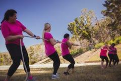 Grupo de mulheres que jogam o conflito durante o treinamento do curso de obstáculo imagem de stock royalty free