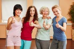 Grupo de mulheres que mantêm os polegares fotos de stock