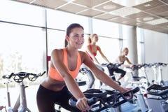 Grupo de mulheres que montam na bicicleta de exercício no gym fotos de stock royalty free