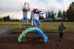 Grupo de niños activos que saltan y que juegan afuera en la escuela p Imagenes de archivo