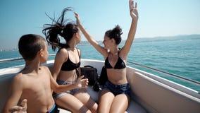 Grupo de niños adolescentes jovenes que van de fiesta y que bailan en un barco de navegación con las manos para arriba Foto de archivo