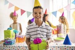 Grupo de niños adorables que se divierten en la fiesta de cumpleaños Niño africano en el frente imagenes de archivo