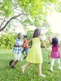 Grupo de niños alegres que juegan en el parque Fotografía de archivo