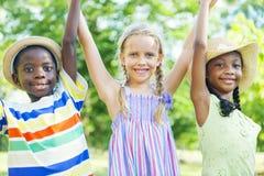 Grupo de niños alegres que llevan a cabo las manos imagen de archivo libre de regalías